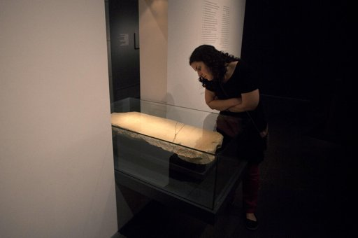 """A museum worker looks at the """"Gabriel Stone"""" as it is displayed at the Israel Museum in Jerusalem, Tuesday, April 30, 2013. An ancient stone with mysterious Hebrew writing and featuring the archangel ..."""